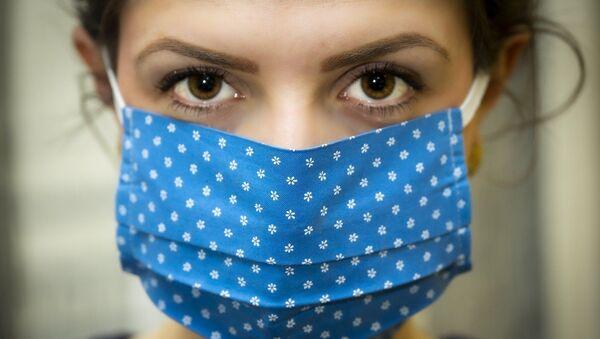 Une femme portant un masque - Sputnik France