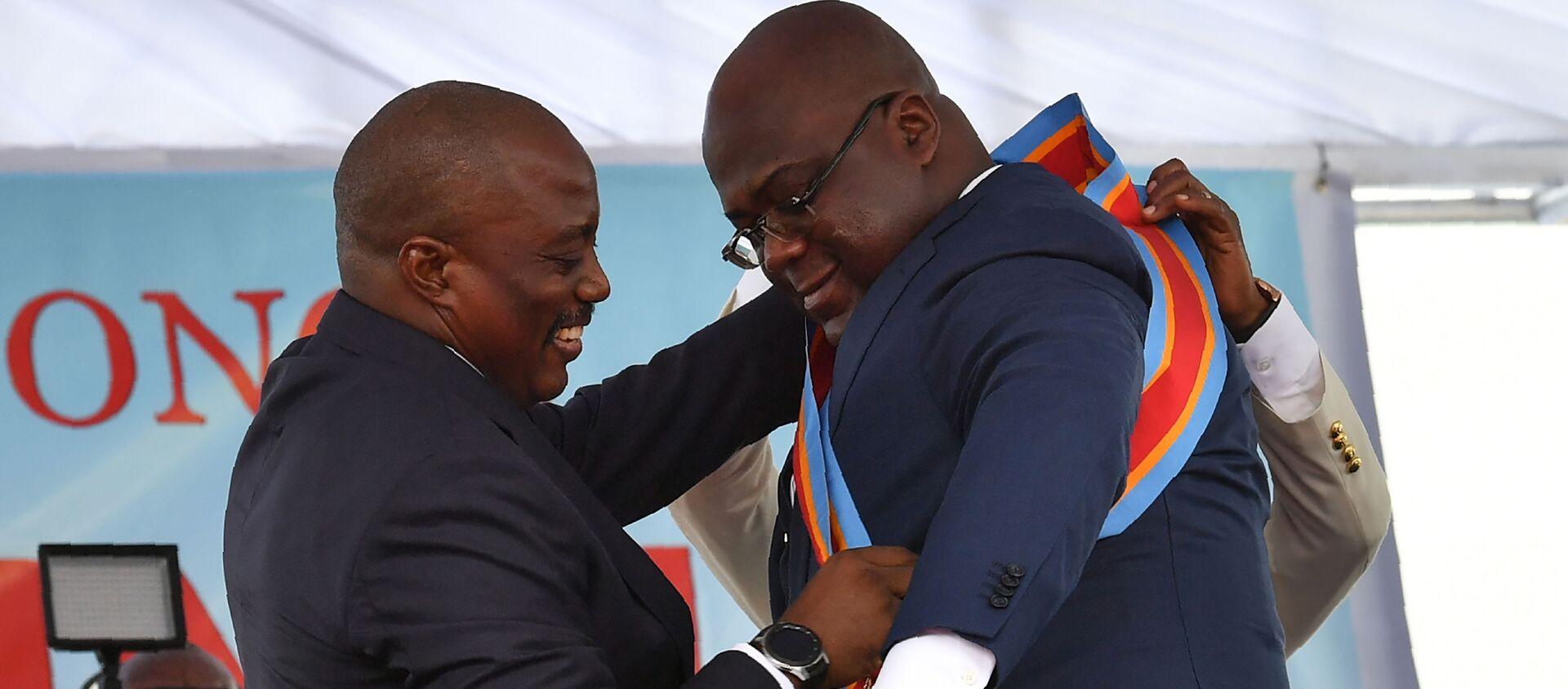 Le Président sortant de la RDC Joseh Kabila aide le nouveau Président Felix Tshisekedi à ceindre l'écharpe. - Sputnik France, 1920, 11.08.2020