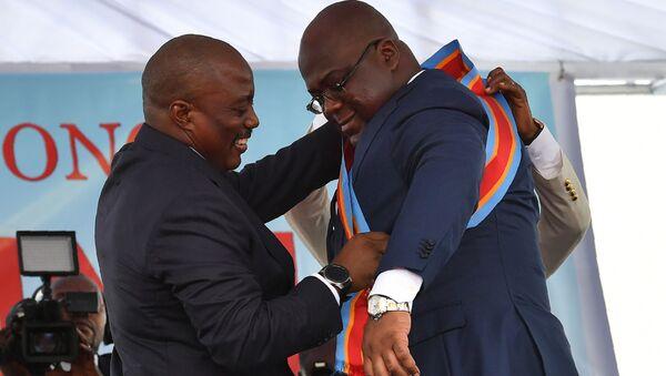 Le Président sortant de la RDC Joseh Kabila aide le nouveau Président Felix Tshisekedi à ceindre l'écharpe. - Sputnik France