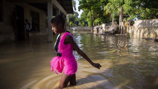 Девочка идет по затопленной после урагана улице на Гаити - Sputnik France