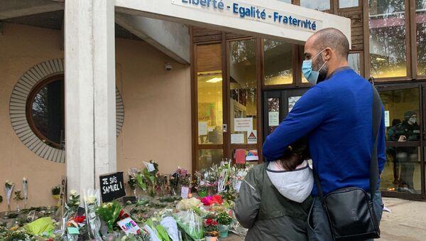 Des enseignants déposent des fleurs devant le collège du Bois d'Aulne à Conflans-Sainte-Honorine en hommage à Samuel Paty, décapité le 16 octobre  - Sputnik France