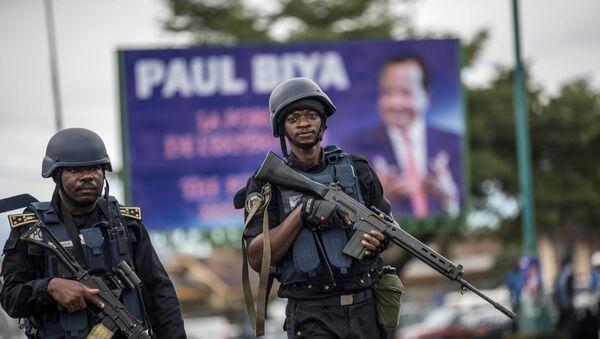 Des militaires camerounais devant une affiche de Paul Biya - Sputnik France