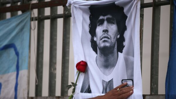 A rose is placed next to a banner of Argentine soccer great Diego Maradona as fans gather to mourn his death, at the Obelisk of Buenos Aires, Argentina November 25, 2020 - Sputnik France
