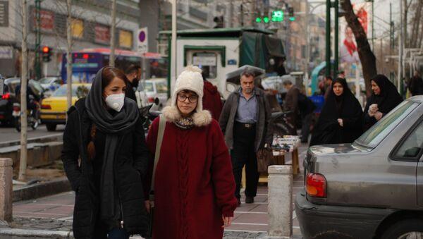 Des habitants de Téhéran marchent dans une rue centrale en portant des masques médicaux. Les autorités iraniennes ont annoncé pour la première fois l'infection par le coronavirus le 19 février. L'infection a commencé dans la ville de Qom, un lieu de pèlerinage pour les musulmans chiites. - Sputnik France