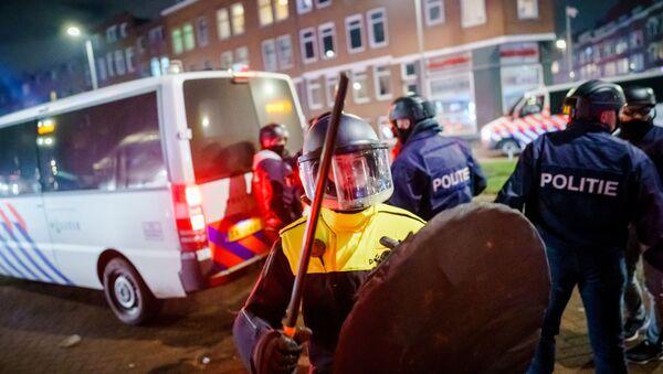Un policier avec un casque et un bouclier tient un bâton alors qu'il se tient à côté d'un policier sur la Beijerlandselaan à Rotterdam, le 25 janvier 2021. - Les Pays-Bas ont été frappés par une deuxième vague d'émeutes le 25 janvier au soir, après que les manifestants se soient à nouveau déchaînés dans plusieurs villes suite à l'instauration d'un couvre-feu pour les coronavirus au cours du week-end. La police anti-émeute a affronté des groupes de manifestants dans la ville portuaire de Rotterdam, où ils ont utilisé un canon à eau. (Photo de Marco de Swart / ANP / AFP) / Netherlands OUT - Sputnik France