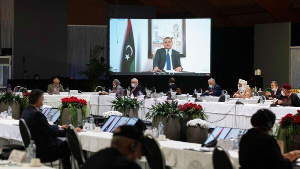 Cette photo prise le 3 février 2021 dans un lieu non divulgué près de Genève et diffusée par les Nations unies (ONU) montre Abdul Hamid Mohammed Dbeibah prononçant un discours par liaison vidéo lors d'une réunion du Forum de dialogue politique libyen (LPDF). - Les délégués libyens aux pourparlers facilités par les Nations unies le 5 février 2021 ont choisi Abdul Hamid Mohammed Dbeibah comme premier ministre de transition, ainsi qu'un conseil présidentiel de trois membres, pour gouverner ce pays d'Afrique du Nord ravagé par la guerre jusqu'aux élections de décembre. (Photo by Handout / UNITED NATIONS / AFP) / RESTRICTED TO EDITORIAL USE - MANDATORY CREDIT AFP PHOTO/ UNITED NATIONS - NO MARKETING - NO ADVERTISING CAMPAGNES - DISTRIBUTED AS A SERVICE TO CLIENTS - Sputnik France