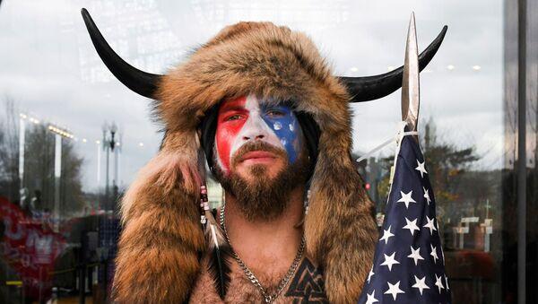 Jacob Anthony Chansley, également connu sous le nom de Jake Angeli, de l'Arizona, pose avec son visage peinturluré aux couleurs du drapeau des États-Unis tandis que les partisans de Donald Trump se réunissent à Washington le 6 janvier 2021 - Sputnik France