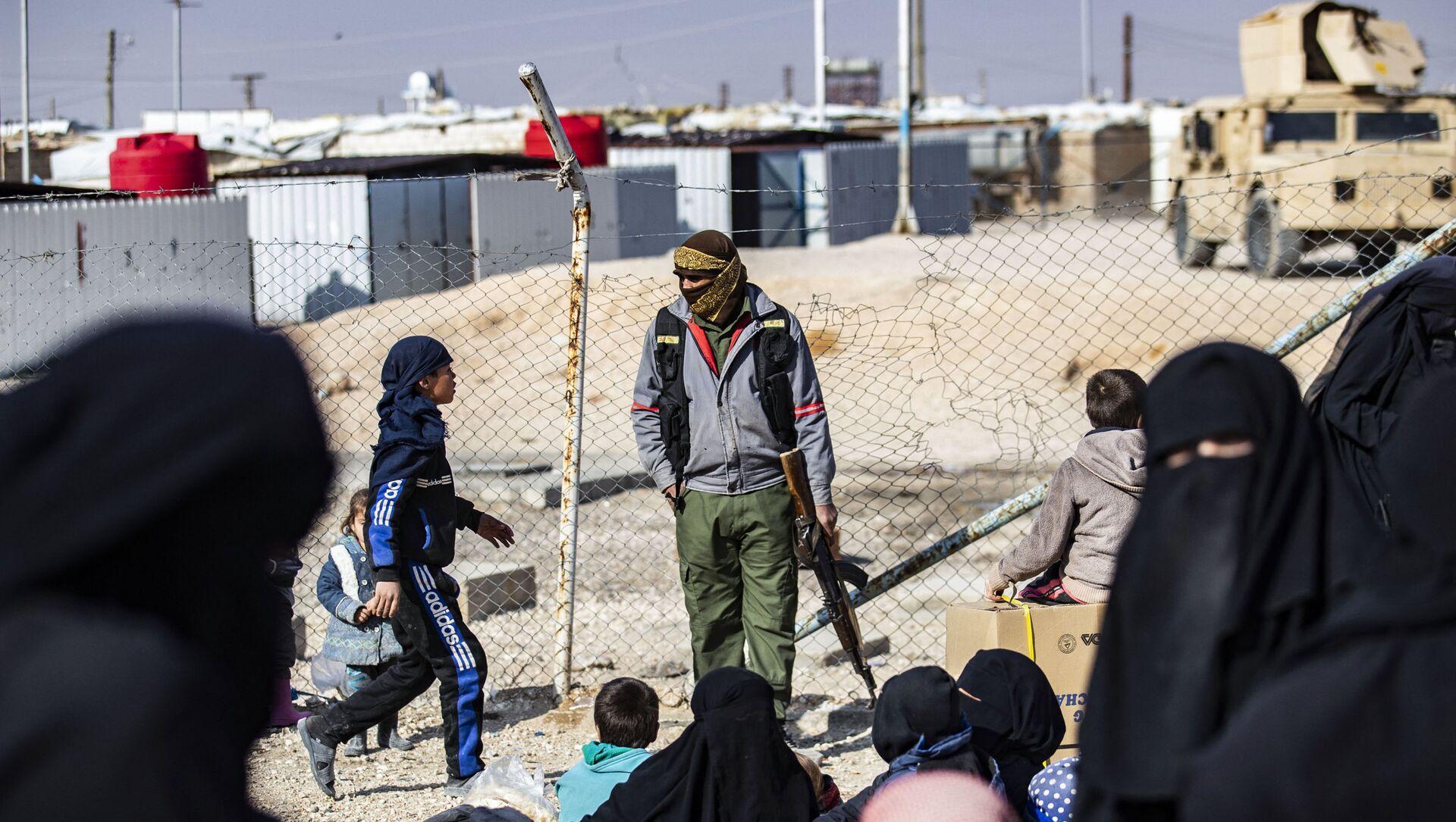 Un membre de la sécurité intérieure kurde monte la garde alors que des femmes conduisent des enfants avant leur départ, lors de la libération d'un autre groupe de familles syriennes du camp kurde d'al-Hol, qui détient des parents présumés de combattants du groupe de l'État islamique (IS), dans le gouvernorat de Hasakeh, au nord-est de la Syrie, le 28 janvier 2021. Delil SOULEIMAN / AFP  - Sputnik France, 1920, 13.02.2021