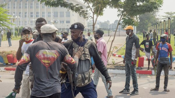 Un manifestant prend à partie un policier lors d'une manifestation à Kinshasa, RDC - Sputnik France