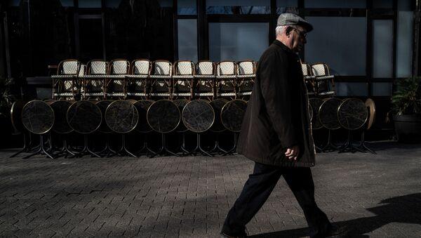 Un homme passe devant un restaurant fermé à Lyon, mars 2020 - Sputnik France