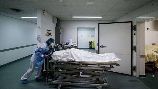 Un membre du personnel médical déplace le corps d'un patient décédé du Covid-19. - Sputnik France