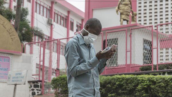 Un homme portant un masque devant l'entrée de l'hôpital de Yaoundé - Sputnik France