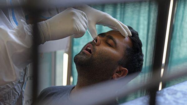 Un agent de santé prélève un échantillon par écouvillonnage nasal sur un homme pour tester le coronavirus Covid-19 à Amritsar en Inde, le 18 avril 2021. - Sputnik France