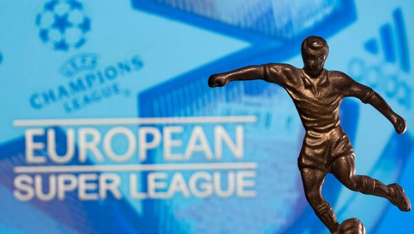A metal figure of a football player with a ball is seen in front of the words European Super League and the UEFA Champions League logo in this illustration taken April 20, 2021 - Sputnik France