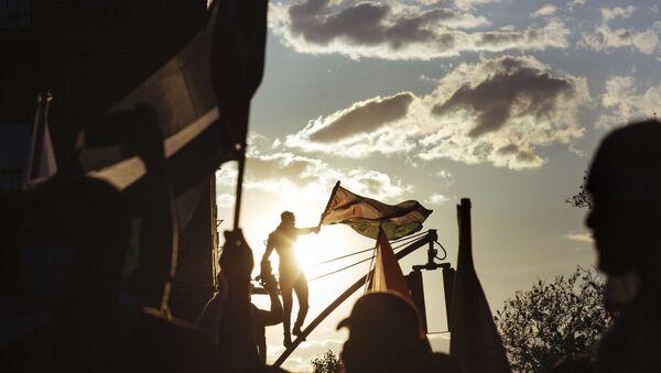 Un activiste au sommet d'un lampadaire brandit un drapeau palestinien lors d'un rassemblement, samedi 15 mai 2021, à New York. Le rassemblement soutient la Palestine dans le conflit actuel entre Israël et la Palestine, le jour où des frappes aériennes israéliennes ont rasé plusieurs bâtiments dans la bande de Gaza.  - Sputnik France