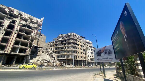 Рекламный щит предвыборной кампании кандидата в президенты Абдаллы Салума Абдаллаха возле поврежденных зданий в Хомсе - Sputnik France