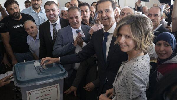 Bachar el-Assad et son épouse dans un bureau de vote lors de la présidentielle syrienne de 2021 (archive photo) - Sputnik France