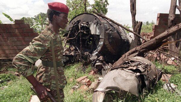 Un militaire rebelle du FPR (Front patriotique rwandais) de Paul Kagame (Tutsi) devant l'épave du Falcon 50 abattu par un tir de missile au-dessus de l'aéroport de Kigali, capitale du Rwanda, le 6 avril 1994. L'avion transportait le Président de la République rwandaise alors en exercice, Juvénal Habyarimana (Hutu), ainsi que son homologue du Burundi, Cyprien Ntaryamira.  - Sputnik France