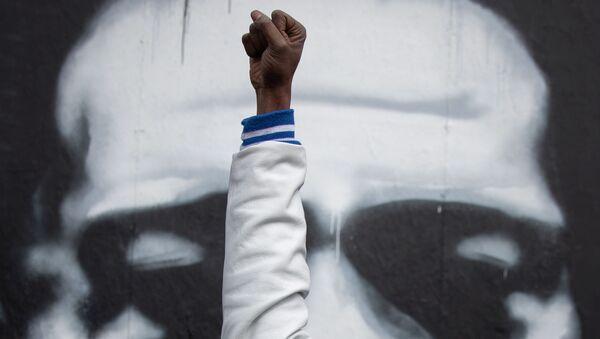 Un Afro-Américain lève sa main devant l'image de George Floyd à Minneapolis, États-Unis, avril 2021  - Sputnik France