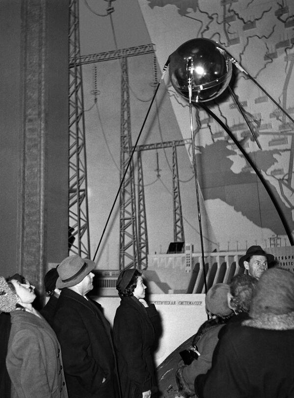 Le 4 octobre 1957, le premier satellite artificiel de la Terre Spoutnik-1 est lancé en URSS. Cet événement marque le début de l'ère spatiale dans l'histoire de l'humanité.Sur la photo: des visiteurs devant une réplique du premier satellite artificiel de la Terre dans le pavillon de la science de l'Exposition agricole de l'union (aujourd'hui Exposition des réalisations de l'économie nationale, VDNKh) à Moscou. - Sputnik France