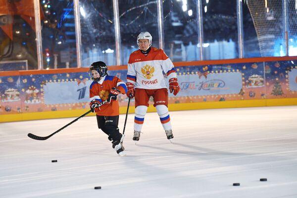 Vladimir Poutine lors d'une séance d'entraînement de hockey sur glace sur la patinoire du GOUM avec Dmitry Achtchepkov, 9 ans, originaire de la région de Tcheliabinsk et participant à la campagne Sapin de vœux, le 21 décembre 2020. - Sputnik France