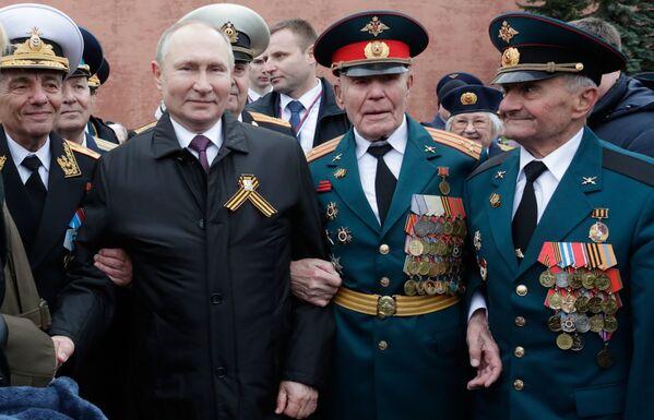 Poutine avec d'anciens combattants après avoir déposé des fleurs sur la tombe du Soldat inconnu dans le jardin Alexandre à l'occasion de la célébration du 76e anniversaire de la Victoire dans la Grande Guerre patriotique, le 9 mai 2021. - Sputnik France