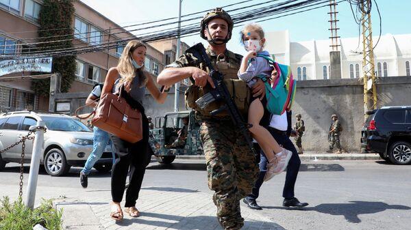 Военнослужащий несет школьника, когда мирные жители бегут из-за перестрелки в Бейруте, Ливан - Sputnik France