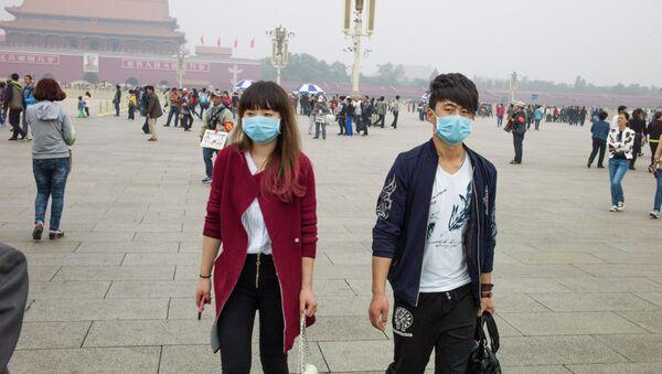 Un couple aux masques respiratoires sur la Place Tiananmen à Pékin - Sputnik France