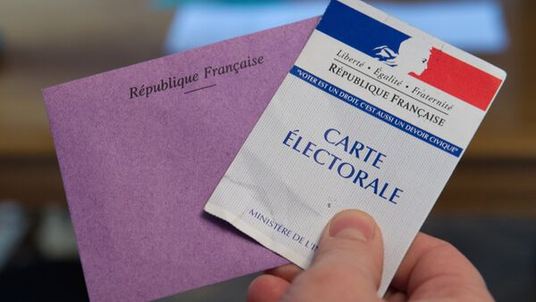 A man holds his electoral card and a ballot as he votes in the second round of the legislative by-election in the 4th constituency of the Doubs in Pont-de-Roide on February 8, 2015. - Sputnik France
