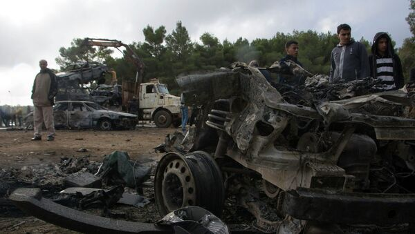 People stand around the wreckage of a vehicle near the site of a bomb blast in Shahat, eastern Libya, November 9, 2014 - Sputnik France