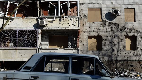 A man drives a car in front of a damaged building in Donetsk, on February 12, 2015 - Sputnik France
