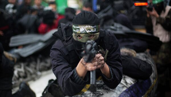 A Palestinian Hamas masked gunman shows his military skills during a rally to commemorate the 27th anniversary of the Hamas militant group, in Gaza City, Sunday, Dec. 14, 2014 - Sputnik France