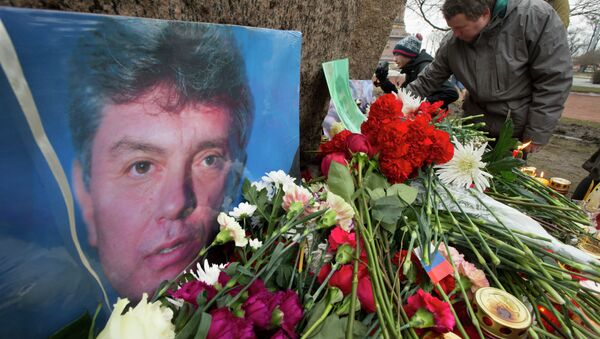 People lay flowers in memory of Boris Nemtsov, seen at left, at the monument of political prisoners 'Solovetsky Stone' in central St. Petersburg, Russia, Saturday, Feb. 28, 2015. - Sputnik France