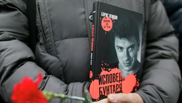 A visitor holds flowers and a book Confessions of the Rebel by Russian leading opposition figure Boris Nemtsov while waiting to attend a memorial service before the funeral of Nemtsov in Moscow, March 3, 2015. - Sputnik France