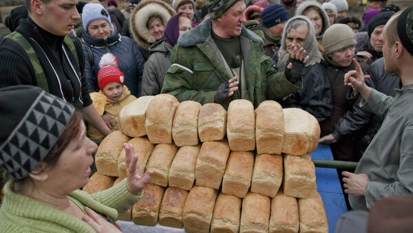A man speaks to a crowd of residents warning them not to push as they wait to get bread, one per person, baked by Russia-backed separatists in Chornukhyne, Ukraine, Monday, March 2, 2015 - Sputnik France