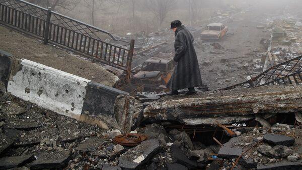 An elderly woman walks across a destroyed bridge, fallen onto the road towards the airport, the scene of heavy fighting in Donetsk, Ukraine, Sunday, March 1, 2015 - Sputnik France