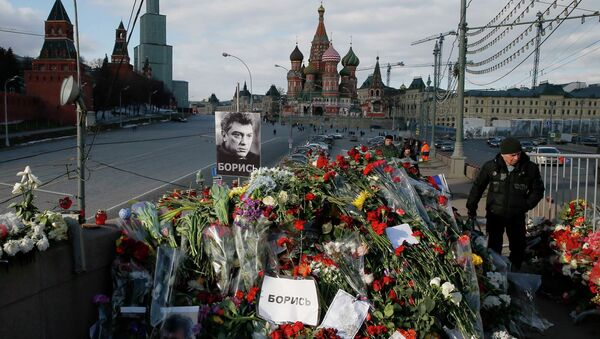 A man walks past flowers at the site where Kremlin critic Boris Nemtsov was murdered on February 27, at the Great Moskvoretsky Bridge, with St. Basil's Cathedral seen in the background, in central Moscow March 6, 2015. - Sputnik France