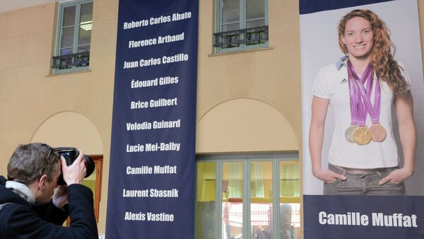 A photographer takes pictures of a giant poster of late French Olympic swimmer Camille Muffat - Sputnik France