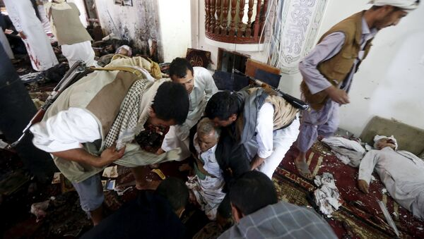 People help an injured man at the scene of a suicide bombing inside a mosque in Sanaa March 20, 2015 - Sputnik France
