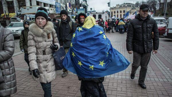 Женщина, обернувшаяся во флаг ЕС, идет по Крещатику в Киеве. - Sputnik France