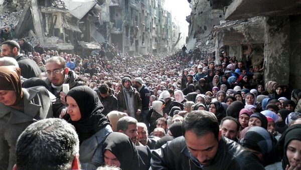 Residents of the besieged Palestinian camp of Yarmouk, queuing to receive food supplies, in Damascus, Syria. - Sputnik France