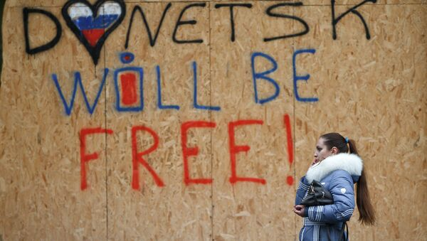 A woman walks by shop windows protected from possible shelling with wooden boards with the inscription Donetsk will be free in Donetsk, Ukraine, Sunday, March 1, 2015 - Sputnik France