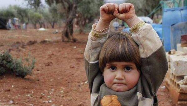 Little Adi Hudea raises her hands in surrender after confusing photographer Osman Sagirli's camera for a gun - Sputnik France