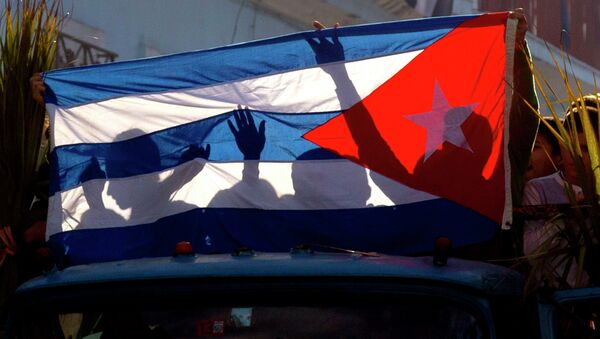 Children's shadows are cast on a Cuban national flag as they take part in a caravan tribute marking the 56th anniversary of the original street party that greeted a triumphant Castro and his rebel army, in Regla, Cuba, Thursday, Jan. 8, 2015 - Sputnik France