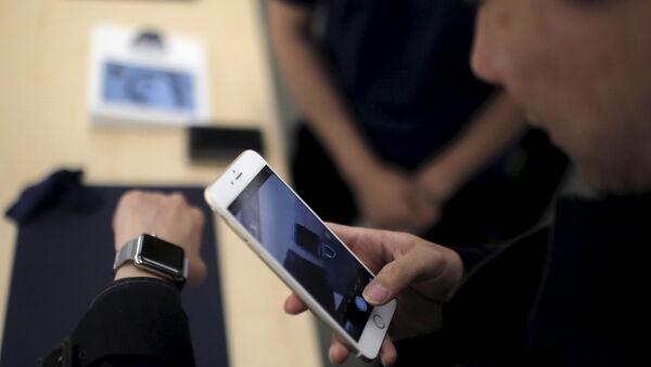 Un client prend une photo d'une montre Apple avec son téléphone portable après dans un Apple Store au centre-ville de Shanghai, le 10 avril 2015 - Sputnik France