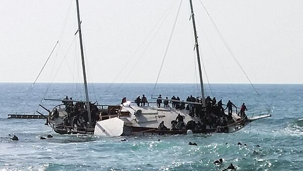Migrants, who are trying to reach Greece, are seen onboard a capsized sailboat, as others are seen in the water trying to reach the coast of the southeastern island of Rhodes April 20, 2015 - Sputnik France