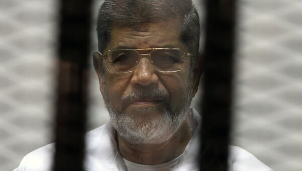 Egyptian ousted Islamist president Mohamed Morsi looks on from behind the defendants cage during his trial. File photo. - Sputnik France