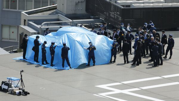 Police and security officials stand around a tarpaulin covering a drone on the roof of Prime Minister Shinzo Abe's official residence in Tokyo April 22, 2015 - Sputnik France