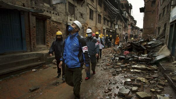 Local volunteers from the Bhaktapur district Red Cross chapter walk past damaged buildings following an earthquake in Bhaktapur near Kathmandu, Nepal in this Red Cross handout picture taken on April 28, 2015. - Sputnik France