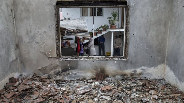 People stand by a destroyed house in Kumanovo, Macedonia, May 11, 2015 - Sputnik France